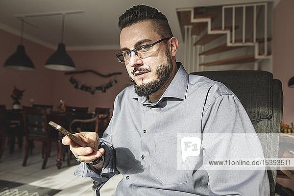 Porträt eines bärtigen Mannes  der zu Hause bei Sonnenschein sein Handy in der Hand hält