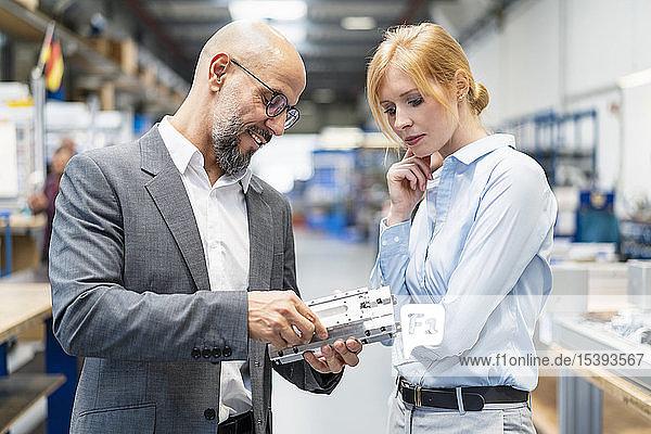 Geschäftsmann und Geschäftsfrau untersuchen Werkstück in Fabrik