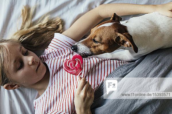 Mädchen liegt auf dem Bett und sieht zu  wie ihr Hund am Lolli leckt