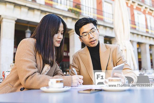 Spanien  Madrid  junges Paar telefoniert und macht Notizen in einem Café auf der Plaza Mayor