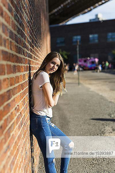 Junge Frau lehnt an Backsteinmauer in New York City
