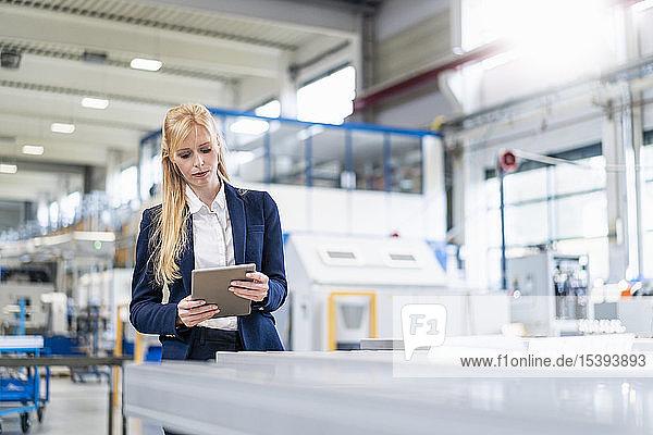 Geschäftsfrau benutzt Tablette in Fabrik
