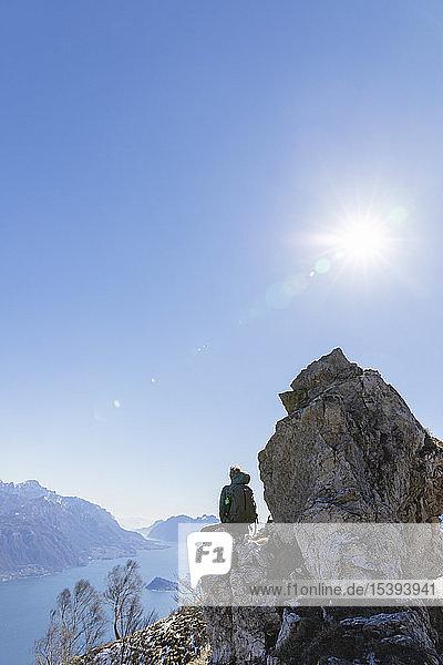 Italien  Como  Lecco  Frau auf Wanderung in den Bergen über dem Comer See  auf einem Felsen sitzend und die Aussicht geniessend