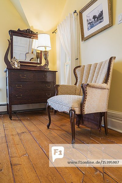 Antique sculpted wood and upholstered armchair  dresser with mirror in guest bedroom with oil stained fir floorboards inside an old 1900 Victorian Queen Anne revival style house  Quebec  Canada. This image is property released.