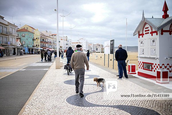 People on the beach walk of Nazare  Portugal.