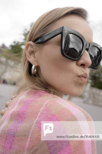 Stylish blogger woman during fashion week  lips forming kiss  in city Paris  France  in city Paris  France