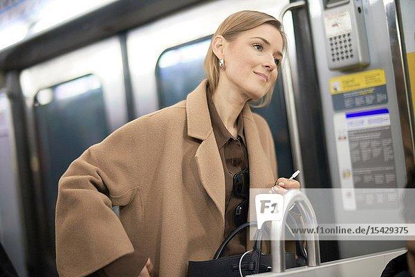 Fashionable blogger woman using public transportation in city Paris  France