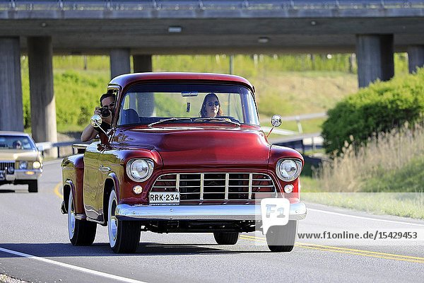Salo  Finland. May 18  2019. Woman drives a mid-1950s Chevy pickup  the male passenger is photographing on Salon Maisema Cruising 2019. Credit: Taina Sohlman/agefotostock