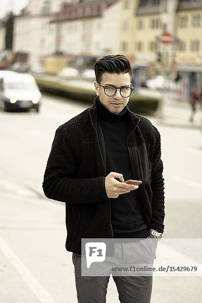 Young man using phone in city  wearing glasses  in Munich  Germany.