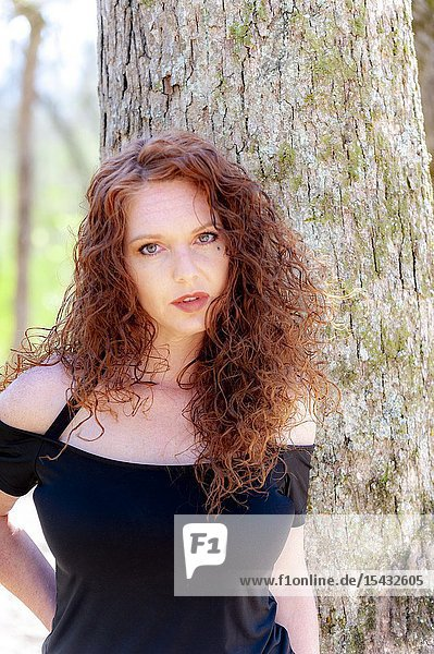 Portrait of a beautiful redheaded woman looking directly at the camera  outdoors.