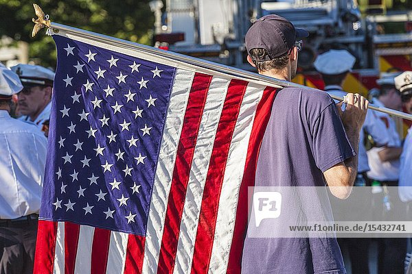 USA  New England  Massachusetts  Cape Ann  Rockport  Rockport Fourth of July Parade  young man with US flag  NR.