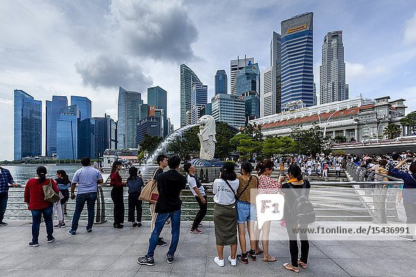 Tourists Taking Photos Of The Merlion Statue and Singapore Skyline  Singapore  South East Asia.