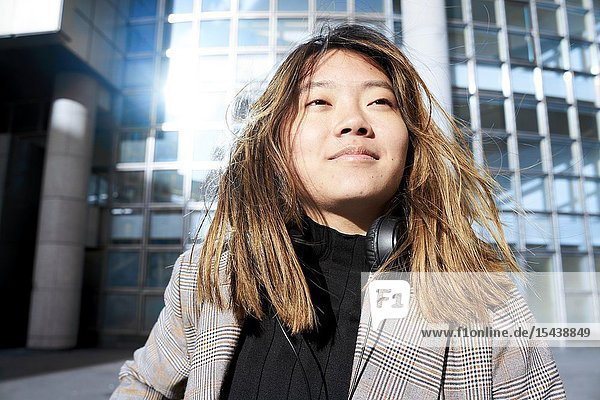 Young confident Asian woman in business district in Paris  France.