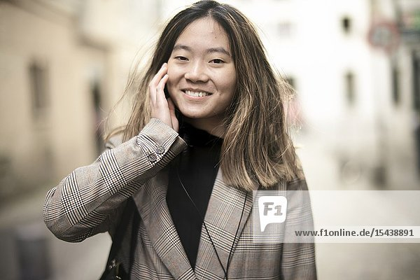 Young coy Asian woman touching her cheek at street  in Paris  France.