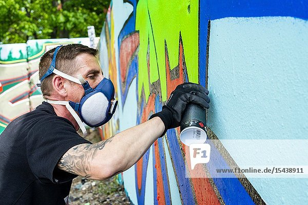 Berlin  Germany. Graffity artist creating jet another piece of urban art on parts of the former Belin Wall  bordering former East-Germany or DDR.