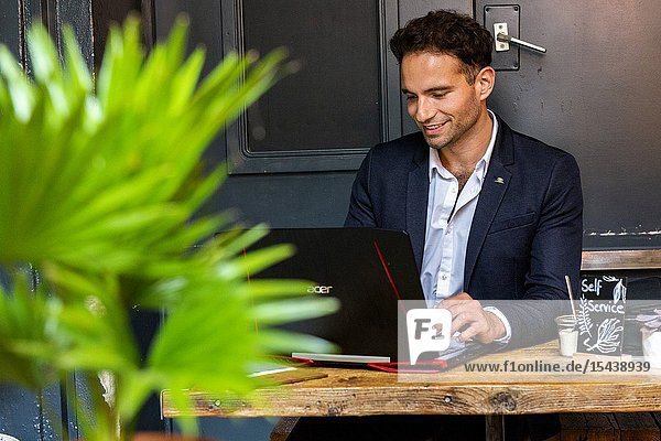 Berlin  Germany. Young Adult & Gay Professional working with his laptop computer and smartphone inside a coffee place to help out his customers with their online marketing and seo.