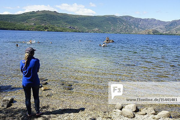 A girl watches as the friends bathe and play in the water of the lakes of Sanabria