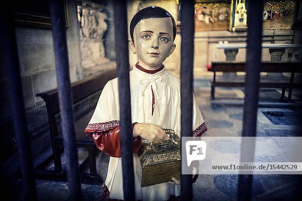 Figure of an altar boy seen through a gate in a church. Tarragona  Catalonia  Spain  Europe.