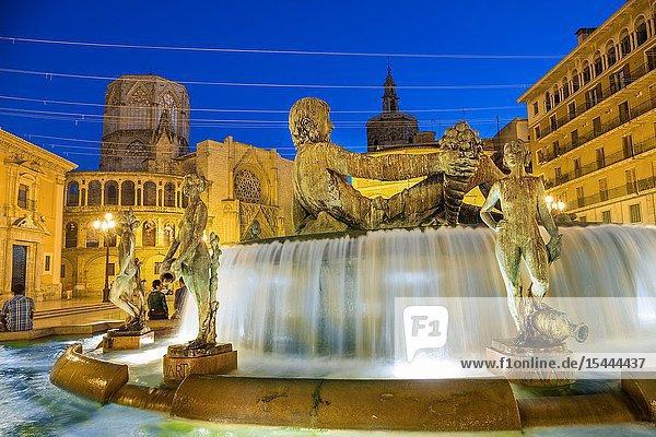 Turia fountain with the Virgen de los Desamparados Basilica and Santa Maria de Valencia Cathedral in the background. Plaza de la Virgen. Virgin Square at dusk  old area of city  Valencia  Comunidad Valenciana. Spain..