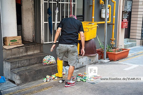 Singapore  Republic of Singapore  Asia - A man in Chinatown is crushing empty beverage cans with a rubber boot.