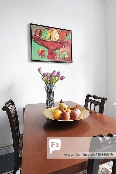 Kitchen dining table with three empty chairs  fruit bowl and still-life painting on the wall  Berlin  Germany.