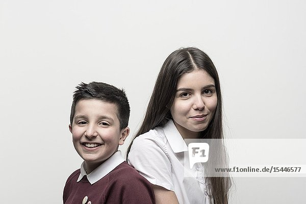 UK England  Portrait of 10 years old boy and his teenage sister   both in school unoforms. Studio settings.
