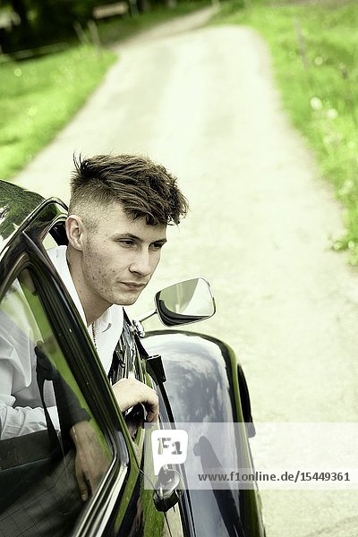 Young man looking out of vintage car at countryside  in Bad Tölz  Germany