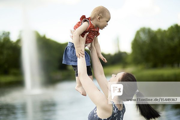 Mother lifting up baby toddler daughter outdoors in park next to water fountain