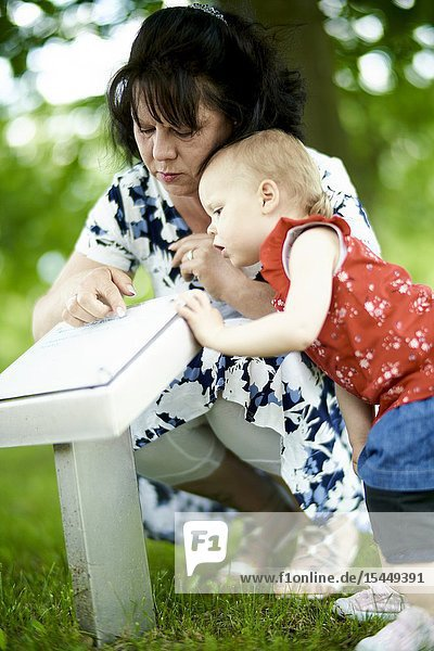 Grandmother with granddaughter baby toddler exploring scientific caption of plants outdoors in park