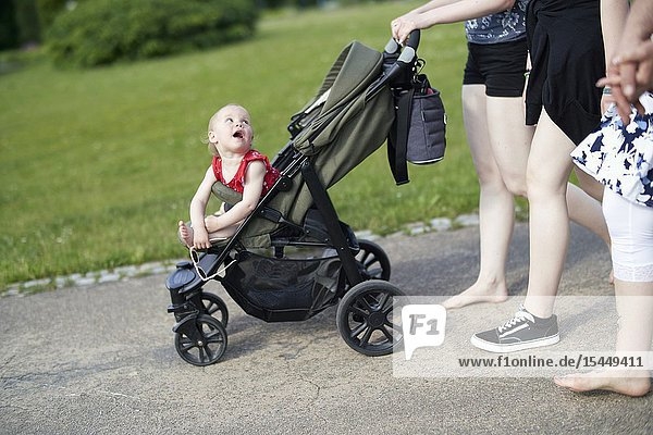 Communicative attentive baby toddler child in buggy looking backwards curiously at mother  walking in park