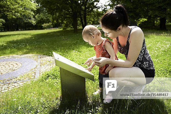 Mother showing daughter baby toddler scientific informatory sign about environment plants outdoors in park