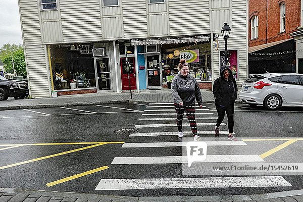 New Milford  Connecticut  USA Two women cross the street in the downtown.