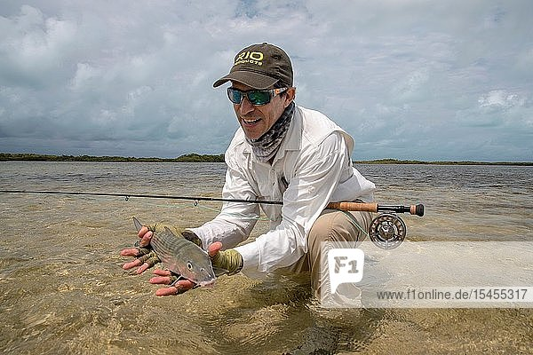 One fly fisherman holding Bonefish on the beach while is fishing in Los Roques National Park Venezuela.