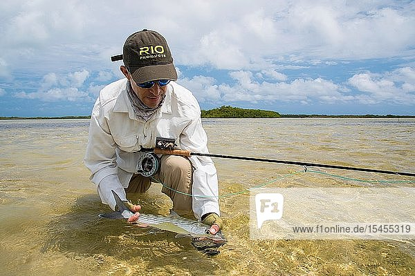 A man fly fisherman holding bonefish fish on the beach in Venezuela Los Roques National Park