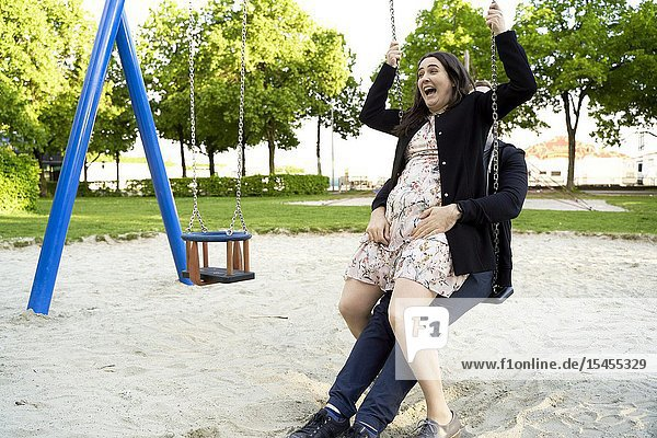 Young excited adult couple sharing swing on children's playground