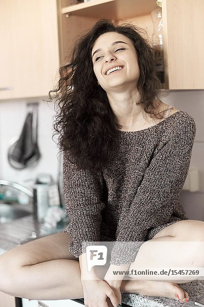 Smiling woman chilling on kitchen unit at home
