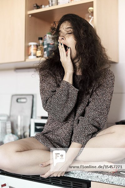 Young slugabed woman yawning  starting day in kitchen