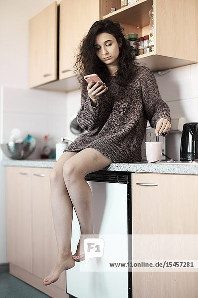 Young woman using smartphone in kitchen at morning  starting day