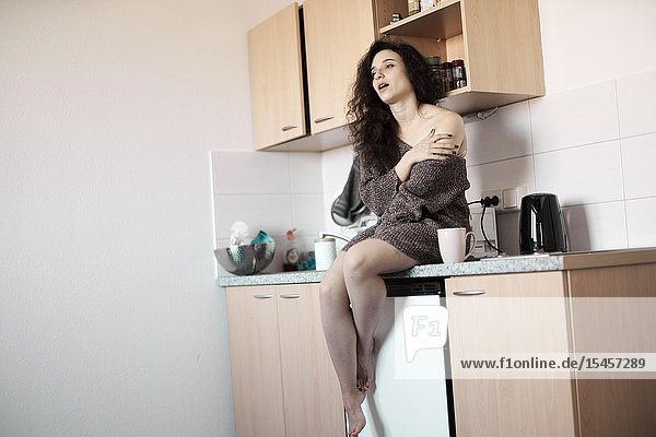 Young woman starting day in kitchen