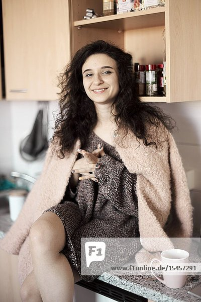 Young woman sitting on kitchen board