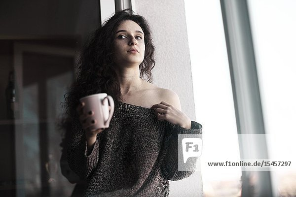 Young thoughtful woman with coffee cup at home