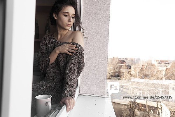 Young sentimental woman sitting on windowsill looking out of window of her home