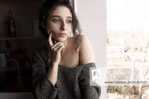 Young wistful woman at home
