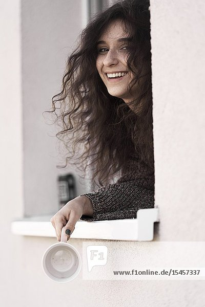 Young happy woman looking out of window of her home