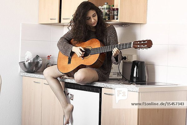 Young woman playing guitar in kitchen at home
