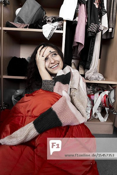 Young optimistic woman in front of her wardrobe