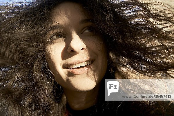 Unvarnished beautiful woman with hair in wind