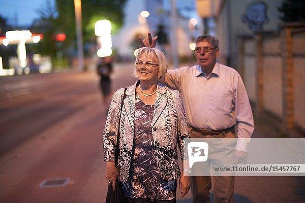 Senior couple walking at street at night in city