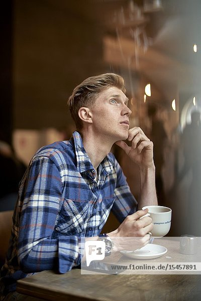 Young man taking break in café and searching for inspiration