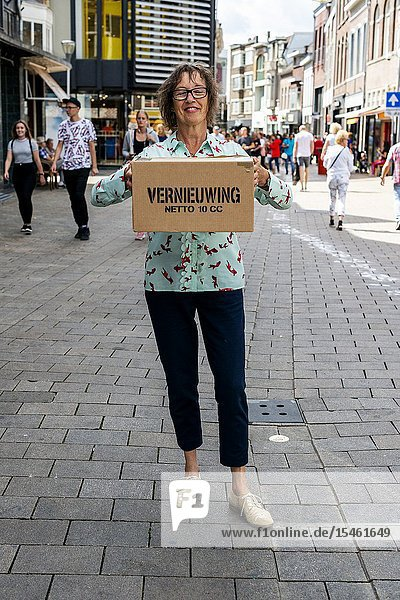 Tilburg  Netherlands. During the CapeTown karton boxes artwork project  all kinds of wishes printed on boxes  were distributed to people passing by. Sjon's Wife distributing one wish box to the Public in the streets of down town.